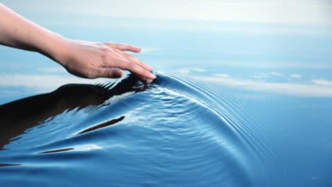 vídeos y material grabado en eventos de stock de a woman uses her hand to create riples in water reflected in a blue sky.  - dedo