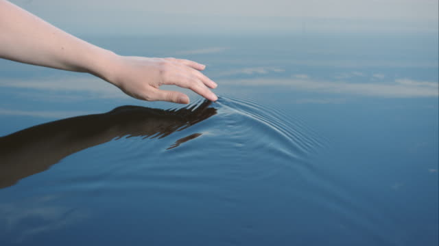a woman uses her hand to create riples in water reflected in a blue sky.  - sensory perception stock videos & royalty-free footage