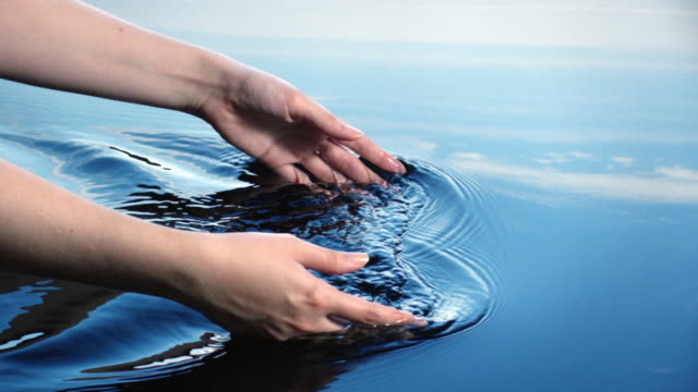 a woman uses her hands to create ripples in water refelcted in a blue sky.  - spa treatment bildbanksvideor och videomaterial från bakom kulisserna