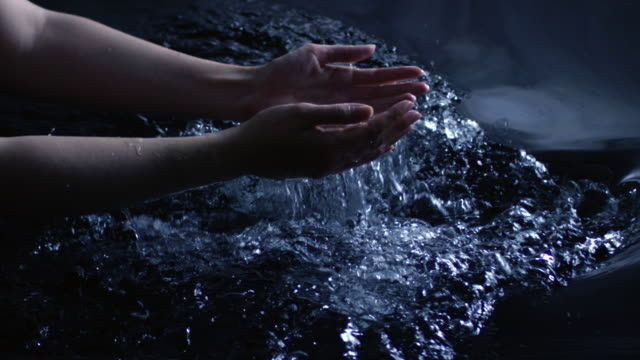 A woman uses her hands to create splashes in water leaving ripples and bubbles refelcted in a moon lit sky.