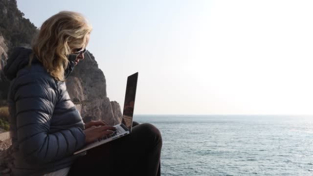 woman uses laptop in rocky perch, above sea - down jacket stock videos and b-roll footage
