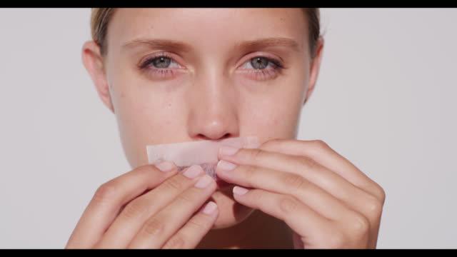 vídeos de stock e filmes b-roll de woman uses lip waxing strip and smiles - depilação