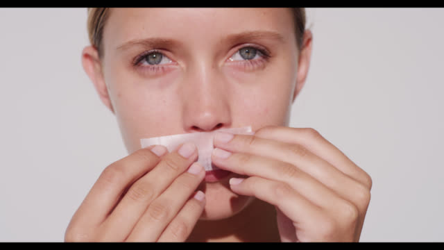 woman uses lip waxing strip and smiles - moustache stock videos and b-roll footage