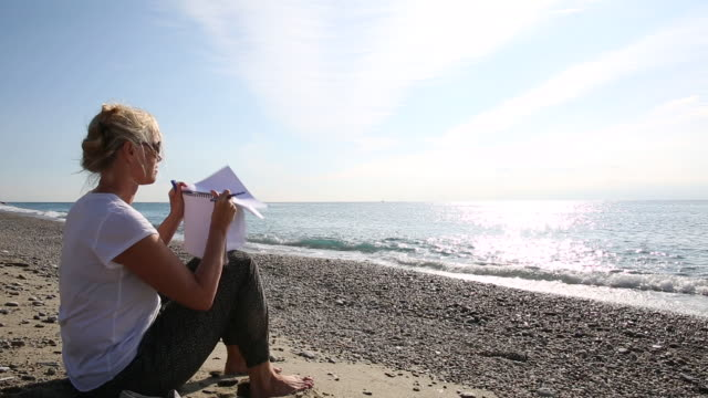 Woman uses sketch book on beach, looks out to sea