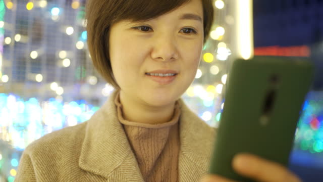woman uses smart phone at night - chinese ethnicity stock videos & royalty-free footage