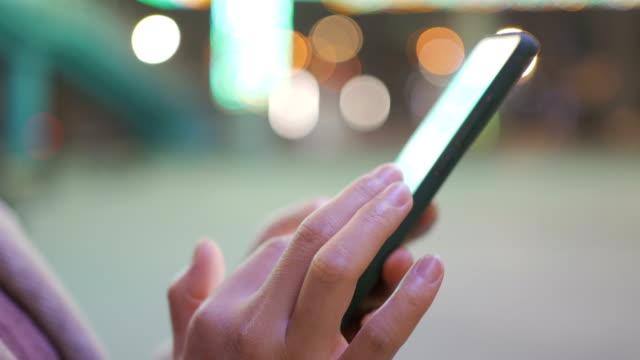 vídeos de stock, filmes e b-roll de mulher usa telefone inteligente à noite - vida urbana