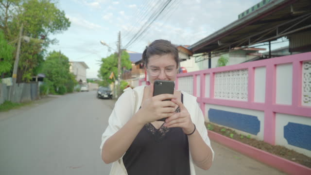 Woman uses smart phone on suburban Thai street