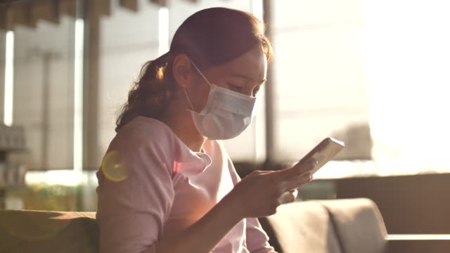 woman uses smart phone with a protective face mask - text stock videos & royalty-free footage