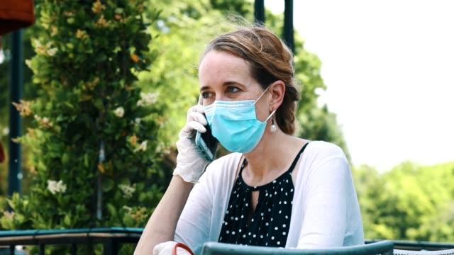 vídeos de stock e filmes b-roll de woman uses smartphone while outdoors during covid-19 pandemic - máscara cirúrgica