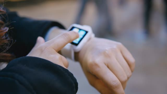 woman uses smartwatch standing on street - wrist watch stock videos & royalty-free footage
