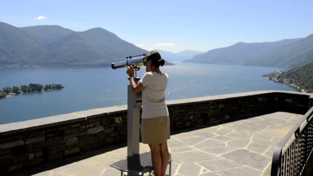 vidéos et rushes de woman uses telescope to admire her surroundings - regarder à travers