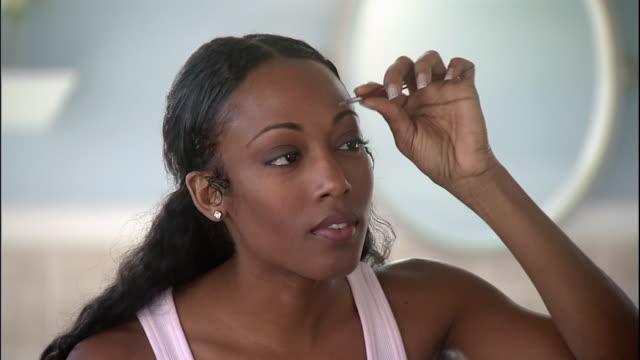 vidéos et rushes de a woman uses tweezers to pluck her eyebrow. - soin du corps