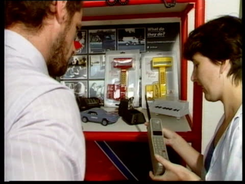 Woman using 1980s mobile phone classic 1980s' portable phones on display and first UK Vodafone shop / INT Customers signing up for portable phones in...