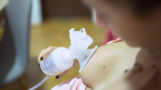 woman using a breast pump - formula video stock e b–roll