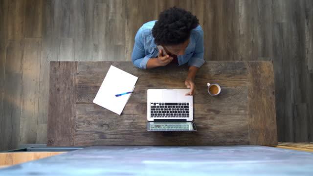 frau mit hilfe eines computers und am telefon sprechen - antworten stock-videos und b-roll-filmmaterial