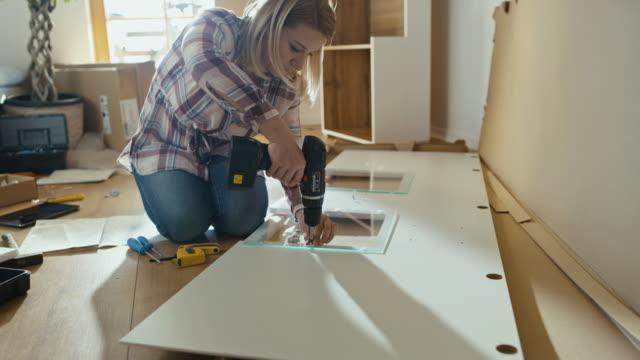 vídeos de stock e filmes b-roll de slo mo woman using a cordless drill while assembling the furniture - broca