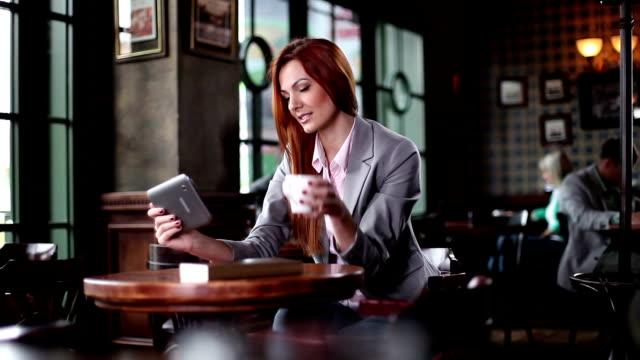 vídeos de stock, filmes e b-roll de mulher usando um tablet digital em um café - equipamento doméstico