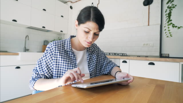 Woman using a digital tablet at home.