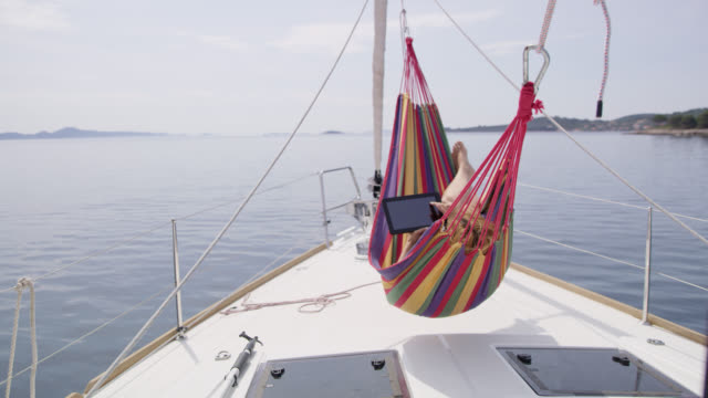 ds ws woman che utilizza un tablet digitale su un'amaca su una barca a vela - andare in barca a vela video stock e b–roll