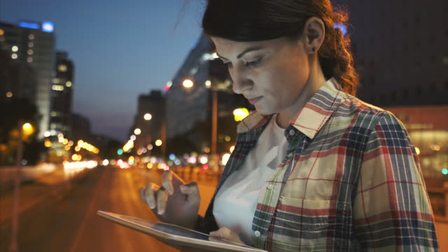 Woman using a digital tablet in the city.