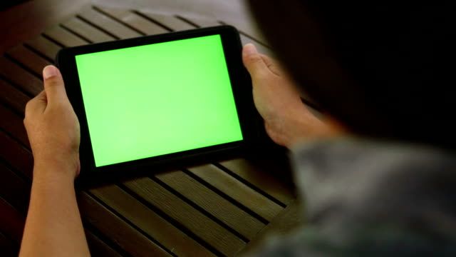 Woman using a digital tablet PC with green screen