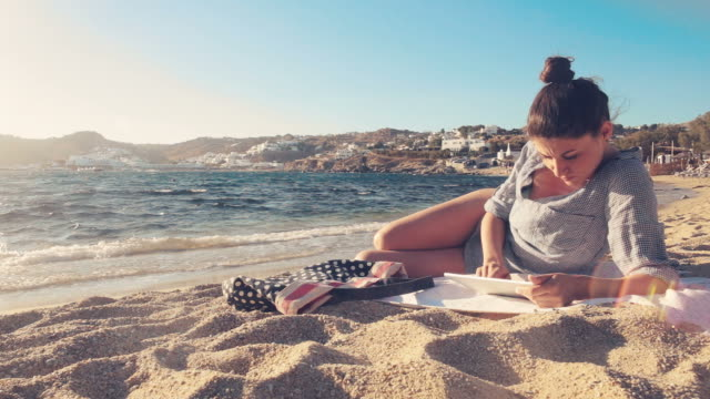 Woman using a digital tablet while relaxing on the beach.