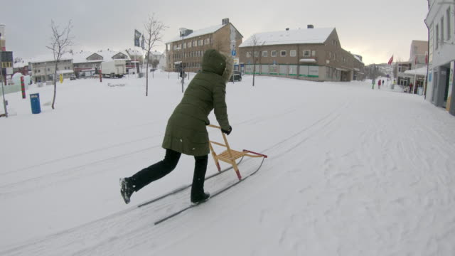 WS Woman using a kick sled in Kirkenes