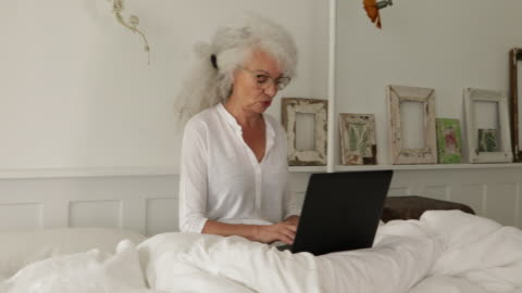 woman using a laptop in bed - white hair stock videos & royalty-free footage