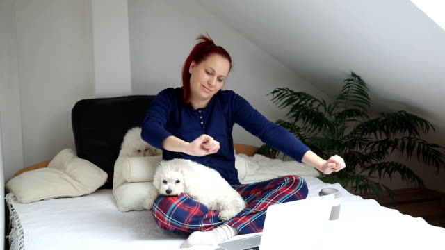 Woman using a laptop with her dog on bed