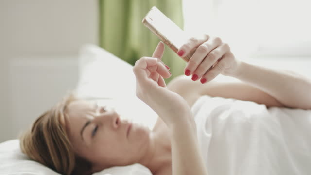 ds woman using a mobile phone in bed - mid adult women stock videos & royalty-free footage