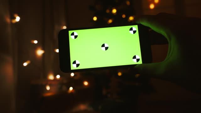 Woman using a mobile phone near Christmas tree.