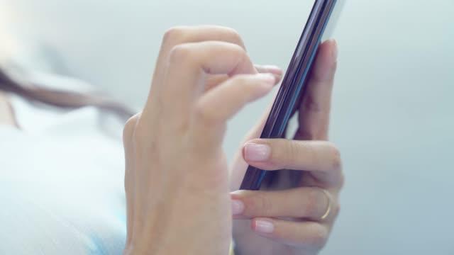 vidéos et rushes de femme à l'aide d'un téléphone mobile relaxant sur banquette-lit extérieur en dehors de la plage jour lunettes chapeau - photo messaging