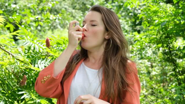 公園で赤い喘息吸入器を使用している女性 - 喘息点の映像素材/bロール