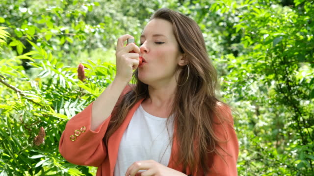 vídeos de stock e filmes b-roll de woman using a red asthma inhaler in the park - asmático