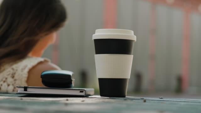 woman using a reusable coffee cup - reusable stock videos & royalty-free footage