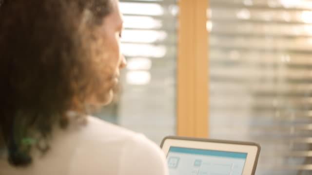 vídeos de stock, filmes e b-roll de mulher usando um aplicativo de controle para casa inteligente em seu tablet para abrir as cortinas em sua sala de estar - parte de uma série