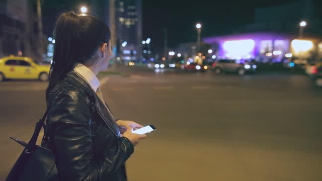 vídeos y material grabado en eventos de stock de mujer utilizando un teléfono inteligente en la ciudad. - mirar alrededor