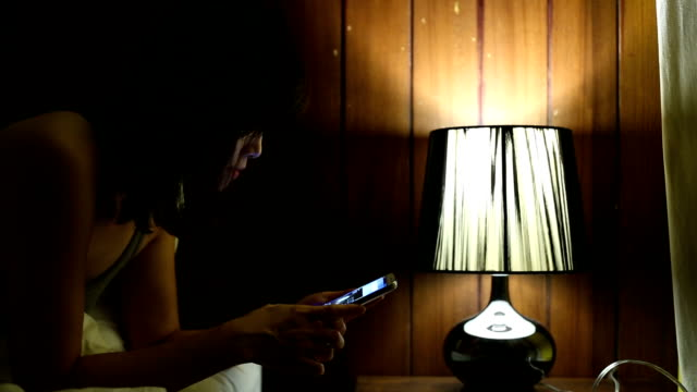 Woman using a smart phone on bed