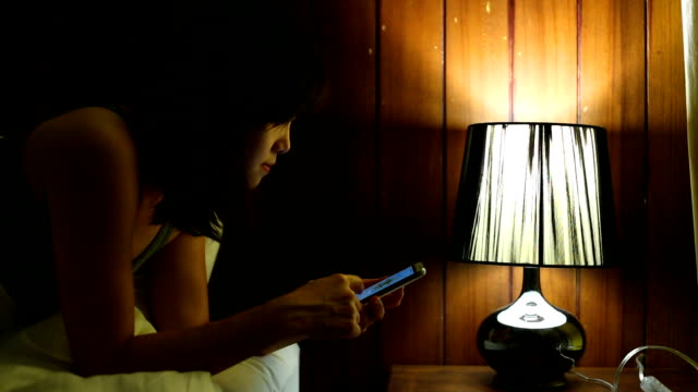 woman using a smart phone on bed - turning on or off stock videos & royalty-free footage