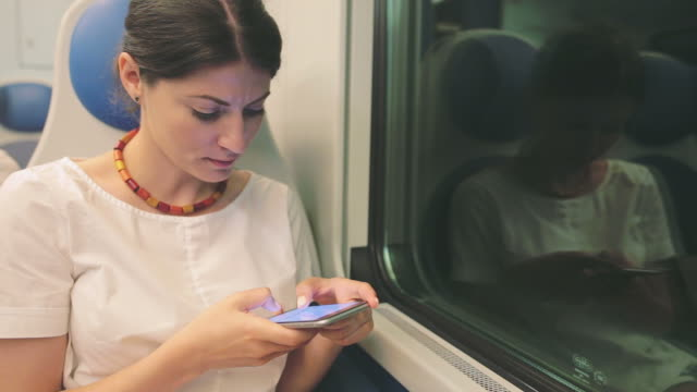 Woman using a smart phone while traveling by train.