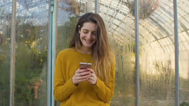 woman using a smartphone outside of a greenhouse - 座る点の映像素材/bロール