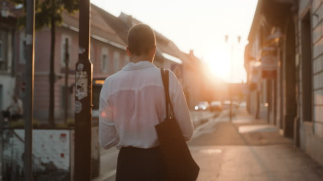 ms woman using a smartphone while walking down the sidewalk - capelli corti video stock e b–roll