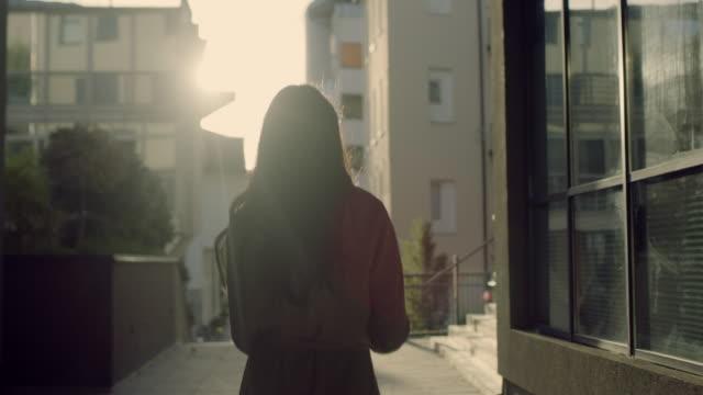 vídeos de stock, filmes e b-roll de mulher do ws que usa um smartphone ao andar na cidade - vista traseira