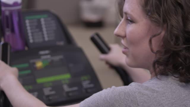 vídeos de stock, filmes e b-roll de woman using a stationary bike at the gym. - cabelo de comprimento médio