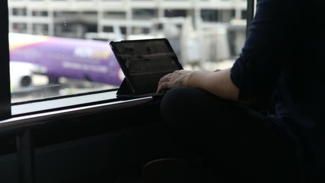 Woman using a tablet at the window in airport