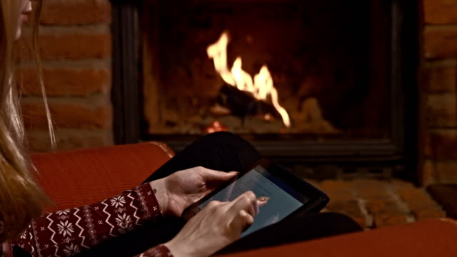 ds woman using a tablet computer by the fireplace - chalet stock videos & royalty-free footage