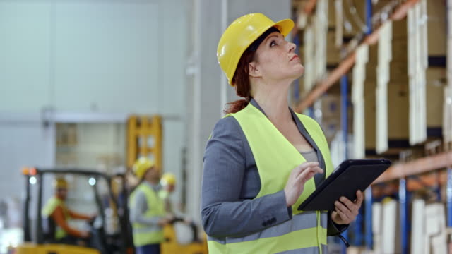 woman using a tablet in the warehouse - coda di cavallo video stock e b–roll