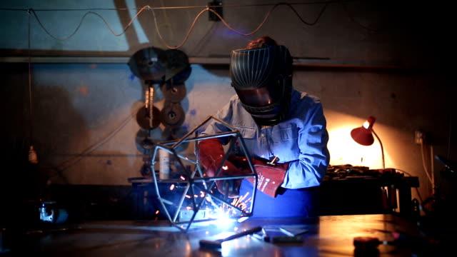 vidéos et rushes de femme à l'aide d'une machine de soudage - sculpture production artistique