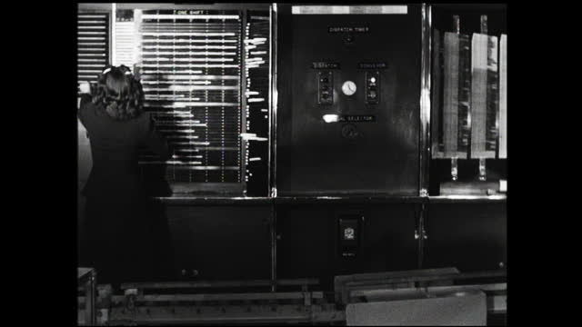 woman using adding machine and trimming label with scissors; woman walks across conveyor belt and put label on the wall, looking at the camera - addierrolle stock-videos und b-roll-filmmaterial