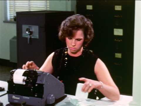 1965 woman using adding machine at desk in office / documentary - rechenmaschine stock-videos und b-roll-filmmaterial